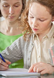 Girl doing prework with her mom Royalty Free Stock Photos