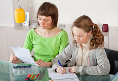 Girl doing prework with her mom. Teenager girl sitting together with her mother and showing her homework Stock Photography