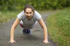 Girl doing push-ups from the ground, a warm up before your jog outdoors. Stock Images