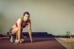 Girl doing push-ups in gym Stock Image