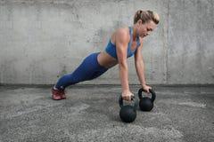 Girl doing push-ups on kettlebells royalty free stock photo