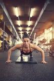 Girl doing pushups exercise stock image