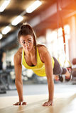 Girl doing pushups in gym royalty free stock photo