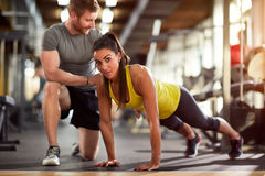Girl doing pushups with trainer`s helps royalty free stock images