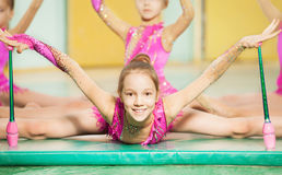 Girl doing rhythmic gymnastics with Indian clubs. Portrait of beautiful preteen girl doing rhythmic gymnastics with Indian clubs, sitting on split on gym mat Royalty Free Stock Image