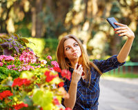 Girl doing self-portrait on the phone. Selfie Royalty Free Stock Image