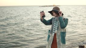 Girl doing selfie on the beach at sunset. young attractive woman in autumn coat takes a picture of herself on a mobile stock footage
