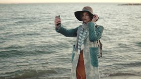 Girl doing selfie on the beach at sunset. young attractive woman in autumn coat takes a picture of herself on a mobile stock video footage