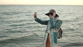 Girl doing selfie on the beach at sunset. young attractive woman in autumn coat takes a picture of herself on a mobile stock video