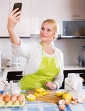 Girl doing selfie at kitchen Stock Images