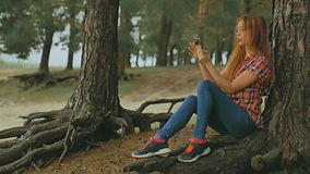 Girl doing selfie on phone smartphone sitting in outdoors  tree slow motion stock footage