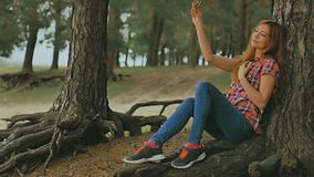 Girl doing selfie on phone smartphone sitting in  tree outdoors slow motion stock video footage