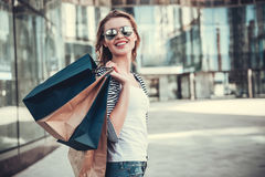 Girl doing shopping. Beautiful girl in sun glasses is holding shopping bags, looking at camera and smiling while walking down the street royalty free stock image