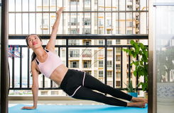 Girl doing side plank yoga position Stock Images