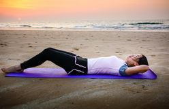 Girl doing situps on the beach at sunset. Outdoors workout Royalty Free Stock Photos