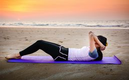 Girl doing situps on the beach at sunset. Outdoors workout Royalty Free Stock Photo