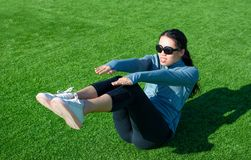 Girl doing situps on the grass, outdoor workout. Girl doing situps on the grass, outdoors workout Royalty Free Stock Photos