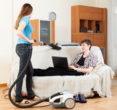 Girl doing sofa cleaning with vaccuum cleaner Royalty Free Stock Photos
