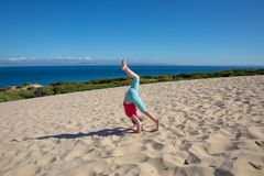 Girl doing the somersault on dune with Africa on the horizon. Four years old girl doing the somersault or handstand on sand dune of Valdevaqueros Tarifa, Cadiz royalty free stock photo