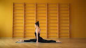 Girl doing split cross twine. Health lifestyle concept. Young woman in black practicing stretching, fitness or yoga. Alone in minimalist yellow studio stock footage