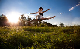 Girl doing split while jumping on field Royalty Free Stock Images