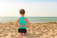 Girl doing sports exercises. On the beach Stock Photo
