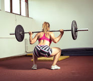 Girl doing squats with weight Royalty Free Stock Photography