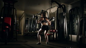 Girl doing squatting with barbell in the gym.