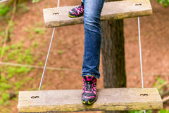 Girl doing step on rope bridge Stock Images