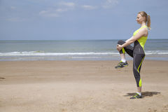 Girl doing stretching exercises on the beach Royalty Free Stock Photo