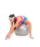 Girl doing stretching exercises on fitness ball. Young girl doing stretching exercises on fitness ball isolated on white Stock Image