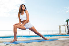 Girl doing stretching exercises outdoors Stock Photo