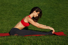 Girl doing stretching legs. Woman practices yoga in nature Stock Photo