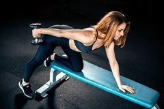 Girl doing triceps exercise with dumbbells stock image