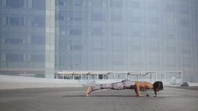 Girl doing upward facing dog pose outdoors. Woman exercising yoga on city street