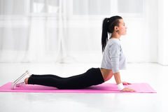 Girl doing warming up exercise for spine, backbend. Arching stretching her back working out at home or yoga class royalty free stock images