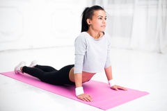 Girl doing warming up exercise for spine, backbend. Arching stretching her back working out at home or yoga class royalty free stock photo