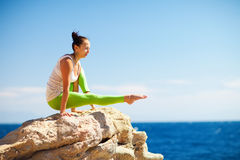 Girl doing yoga on the beach Stock Image
