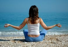 Girl doing yoga on beach. Young attractive female sits on a beach doing yoga with a view of the Adriatic Sea from Gargano National Park in Southern Italy royalty free stock photo