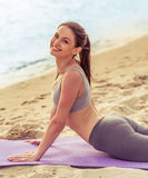 Girl doing yoga on the beach. Beautiful girl in sport clothes is looking at camera and smiling while stretching on yoga mat on the beach Stock Photography