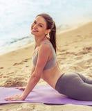 Girl doing yoga on the beach Stock Photography