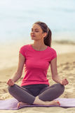 Girl doing yoga on the beach Stock Photo
