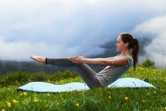 Girl doing yoga exercise balance on lawn in mountains Stock Photos