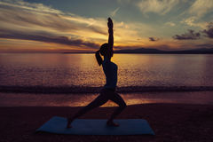 Girl doing yoga exercise on beach. Young woman doing yoga exercise on beach in summer at sunset, concept of healthy lifestyle Royalty Free Stock Images