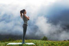 Girl doing yoga exercise on lawn in mountains Stock Photos