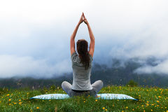 Girl doing yoga exercise lotus pose on lawn in mountains Royalty Free Stock Photos