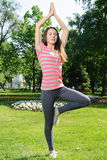 Girl doing yoga exercise outdoors in the park Stock Photography