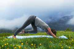 Girl doing yoga exercise strap on the lawn in mountains Royalty Free Stock Photography