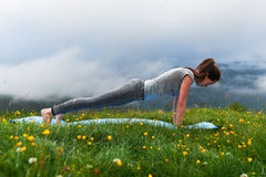 Girl doing yoga exercise strap on the lawn in mountains Royalty Free Stock Photos