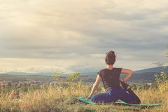Girl doing yoga exercise on top of hill, back view stock images